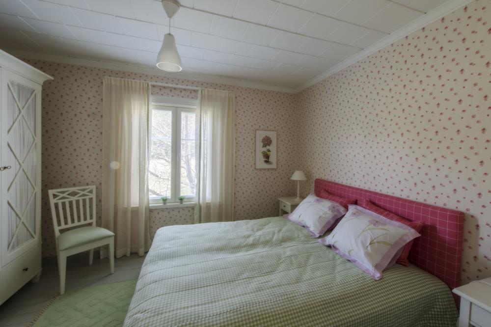 Päärakennuksen ruusuinen makuuhuone.