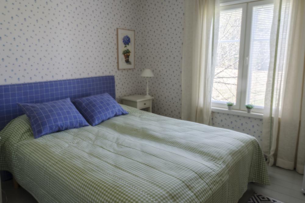 Päärakennuksen viihtyisä ja sinisävyinen makuuhuone.